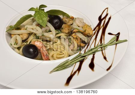 close up of linguine pasta with seafood on white plate