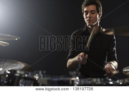Young Drummer Playing Drum Kit In Studio