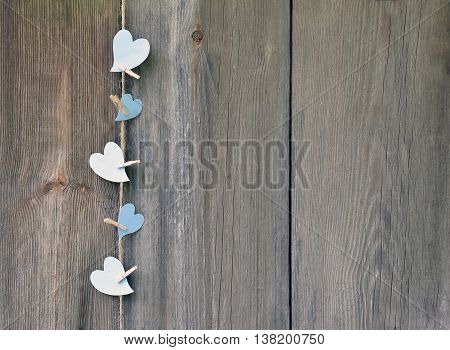 Hearts and clothespins on a coarse cord on an old wooden plank background.Unobtrusive expression of feelings. In rustic style.