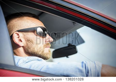 Attractive man in car in sunglasses. Travel concept.