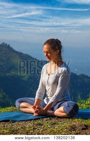 Sporty fit woman practices yoga asana Baddha Konasana - bound angle pose outdoors in HImalayas mountains in the morning with sky. Himachal Pradesh, India