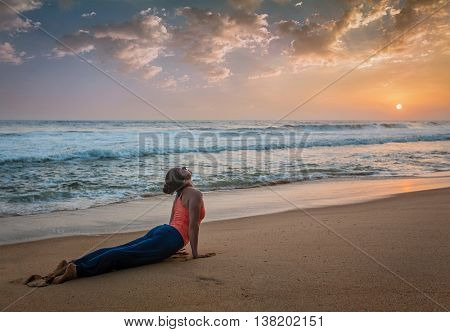 Yoga outdoors on beach - woman practices Ashtanga Vinyasa yoga Surya Namaskar Sun Salutation asana U