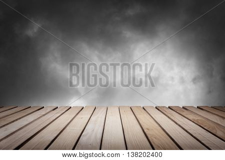 Wood platform and cloudy dark dramatic sky.