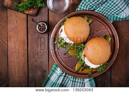 Hamburger (sandwich) With Chicken Burger, Lettuce, Asparagus, Poached Egg And Tartar Sauce. Top View