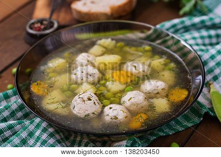 Dietary Soup With Chicken Meatballs And Green Peas In A Glass Bowl On A Wooden Background.