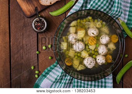 Dietary Soup With Chicken Meatballs And Green Peas In A Glass Bowl On A Wooden Background. Top View