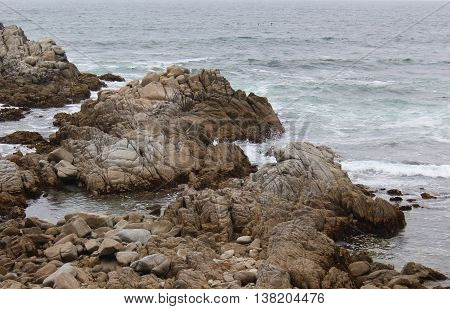 Grey blue water of the Pacific Ocean on a cloudy day gently splashing against the rocky shoreline of Pacific Grove, California in waves of aqua colored water and white foam.