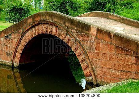 Sanxindui, Sichuan, China - April 29 2006: A coral-colored single arched sandstone bridge spans a canal at the Sanxiungdui Ancient Civilisation Museum