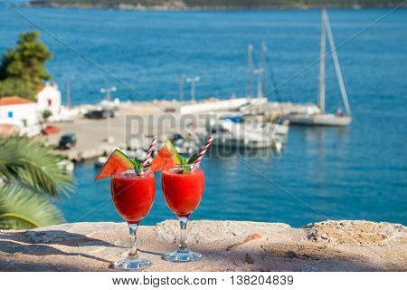 Two watermelon smoothie on the terrace overlooking the marina. Watermelon smoothie on summer holidays by the marina view. Horizontal. Daylight.