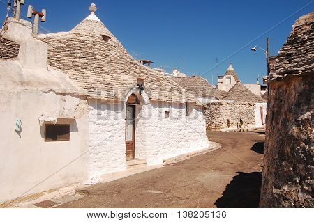 A characteristic street of Alberobello with its famous Trulli in Apulia - Italy