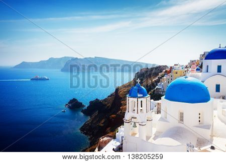 volcano caldera with blue church domes at sunny day, Oia, Santorini, toned