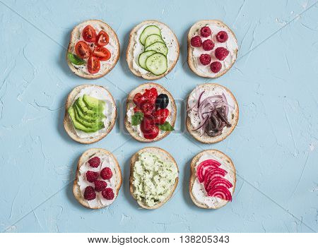 Range of sandwiches - sandwiches with cheese tomatoes anchovies roasted peppers raspberries avocado bean pate cucumber olives. On a blue background top view.
