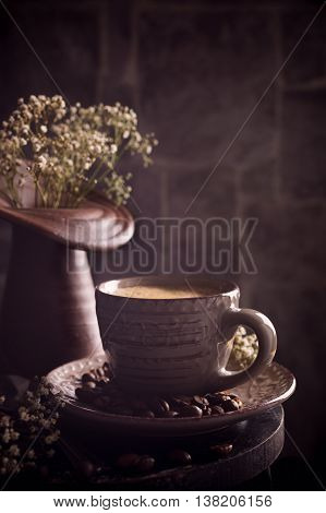 Coffee cup with coffee beans on dark rustic background with space for text