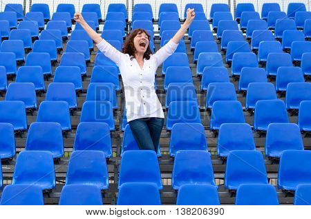 Woman Standing In An Auditorium Cheering