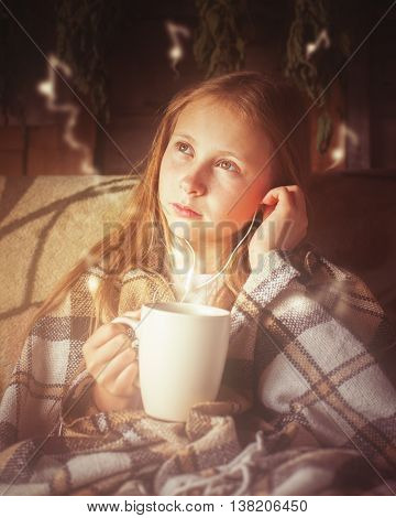Young beautiful girl in a village house with a cup of coffee to enjoy listening to music.
