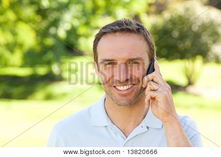 Handsome Man Phoning In The Park
