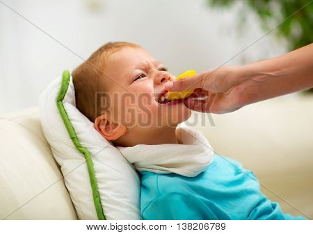 Cold little boy eating a lemon at home
