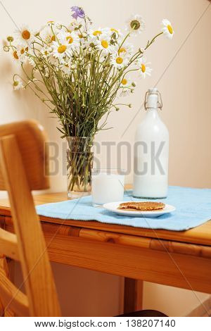 Simply stylish wooden kitchen with bottle of milk and glass on table, summer flowers camomile, healthy food moring concept noone