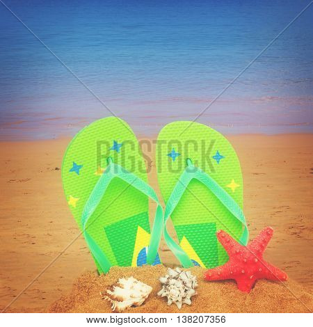 pair of green sandals and starfish in sand isolated on white background, retro toned