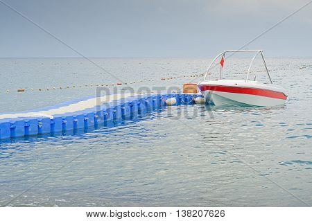 Boat with red flag parking near blue plastic pontoon bridge waiting for tourists in Mediterranean sea.
