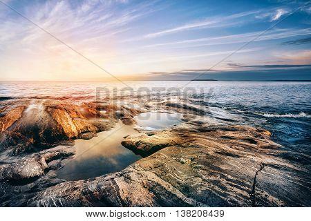 Stone coast of Ladoga lake at sunset. Karelia, Russia.