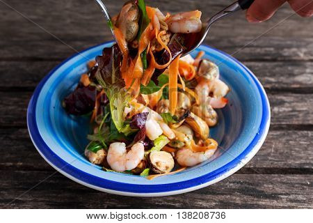 Mussel, shrimp and lettuce Asian style salad with sprinkle of chili