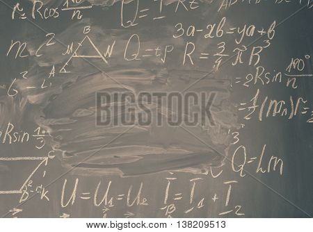 math formulas written in white chalk and copy space on black board, retro toned