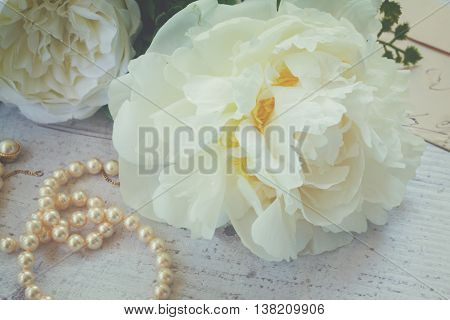 White fresh peony flowers posy with pearls jewellery close up on white wooden table, retro toned