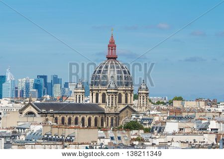 The Saint Augustin church and parisian houses with modern skyscrapers of business La Defense district in the background France.