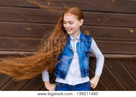 Portrait of beautiful smiling redhead girl with long hair fluttering in the wind