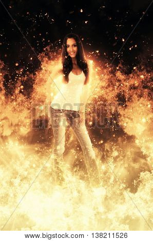 Attractive slender smiling woman standing in amongst fiery hot yellow orange flames with shooting sparks engulfing her in a conceptual image