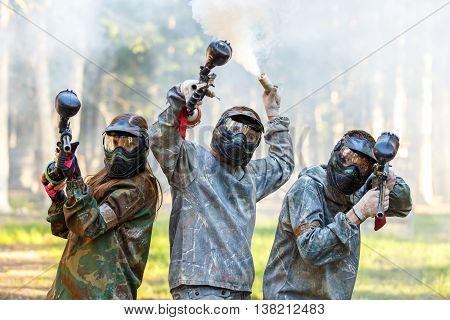Company of friends posing with smoke grenade and paintball markers