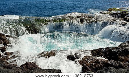 Spontaneous waterfall in natural pool at high tide, coast of Telde, Gran canaria, Canary islands