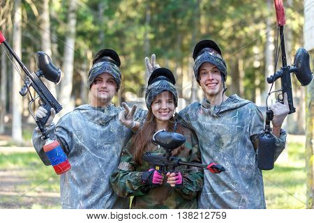 Company of three smiling paintball players posing outdoors