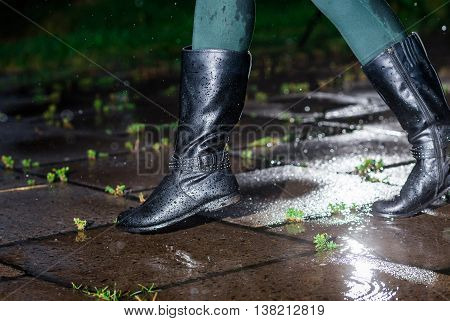 Female legs in black leather high boots on cobble on the edge of rain puddle, closeup. Concept of protection against rainy weather, waterproof footwear.