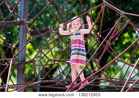 Active little child playing on climbing net and jumping on trampoline at school yard playground. Kids play and climb outdoors on sunny summer day. Cute girl on nest swing at preschool sport center.