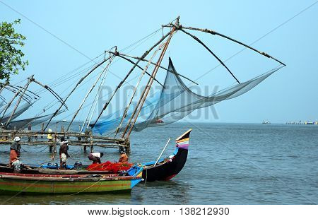 Kochi , Kerala, India - March 23, 2013 - Fishing nets in Cochin symbol. Fishermen and boat departing from the shore in the Indian Ocean in March 23, 2013 in Kochi, Kerala, India