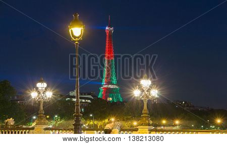 Paris; France-July 06 2016 : The Eiffel tower lit up in colors of Portuguese flag during soccer Europe championship viewed from the Alexandre III bridge.