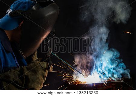 A worker in welder mask is welding metal construction