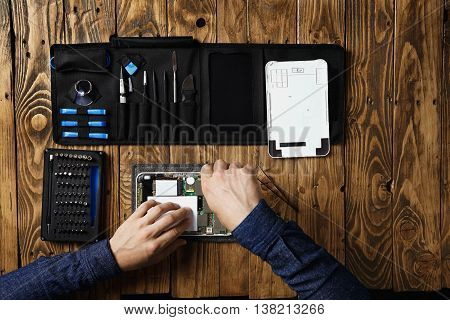 Top view master works on broken tablet to repair it near tool bag and on wooden table in service lab