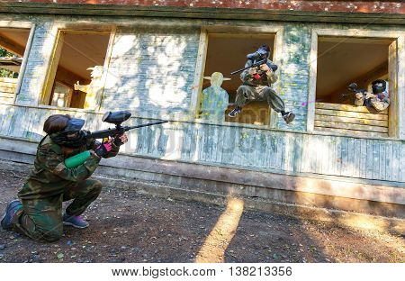 Dynamic paintball battle of three players outdoors
