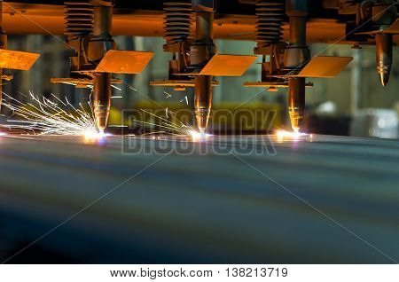 A few oxygen torches are cutting sheet metal a part of CNC machine.