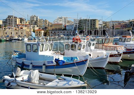 HERAKLION GREECE - MAY 12: The traditional Greek fishing boat are near pier and tourists on May 12 2014 in Heraklion Greece. Up to 16 mlllion tourists are expected to visit Greece in year 2014.