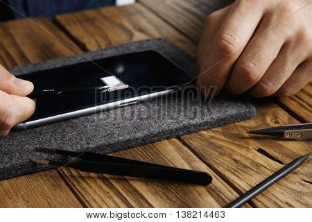 Master holds angled esd tweezers with gsm micro sim card tray above mobile smartphone before fixing it on aged wooden table with rich texture