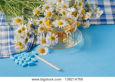 Chamomile Tea In A Transparent Cup And Camomile Flowers On Table.