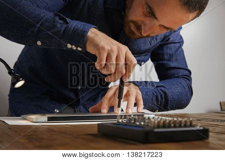 Serviceman uses screwdriver to close backside topcase of personal computer laptop after repairing and cleaning service in his lab