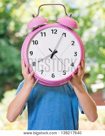 Outdoor portrait of happy teen boy 12-14 year old with big alarm clock. Back to school concept.