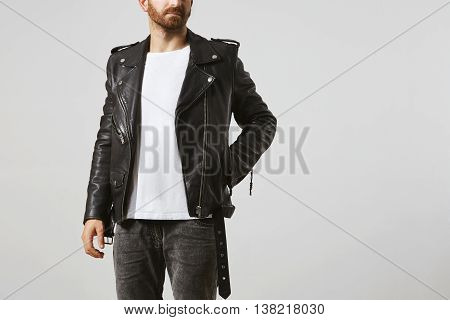 Brutal attractive bearded man in black geniune leather motorcycle jacket poses in white blank t-shirt from premium thin cotton, isolated on white mockup