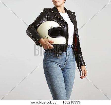 Young attractive woman in high waist jeans , leather motorbike jacket and blank white t-shirt with helmet in hand poses turning around , isolated on white