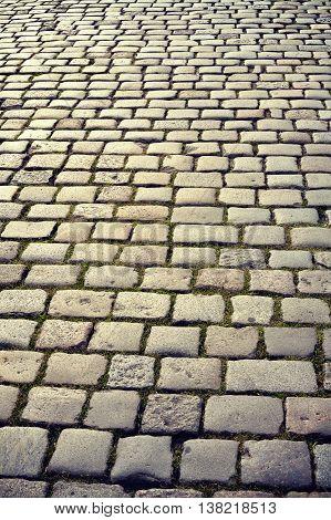 Vintage toned cobblestones at sunrise street in Poznan Poland.